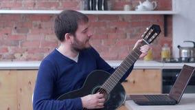 Het muzikale onderwijs, grappige kunstenaarsmens het praktizeren spelgitaar gebruikt laptop computer met online videoleerprogramm stock footage
