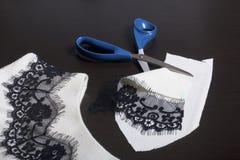 Het naaien en het kleden zich Op dark is de oppervlakte een witte kleding met een zwart die lint voor decoratie wordt genaaid Dic Royalty-vrije Stock Afbeeldingen