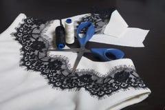 Het naaien en het kleden zich Op dark is de oppervlakte een witte kleding met een zwart die lint voor decoratie wordt genaaid Nab Royalty-vrije Stock Foto