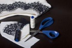 Het naaien en het kleden zich Op dark is de oppervlakte een witte kleding met een zwart die lint voor decoratie wordt genaaid Nab Royalty-vrije Stock Afbeelding