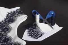 Het naaien en het kleden zich Op dark is de oppervlakte een witte kleding met een zwart die lint voor decoratie wordt genaaid Nab Stock Afbeelding