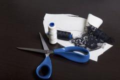 Het naaien en het kleden zich Op een donkere oppervlakte lig schaar, draadspoelen en in orde makende doek royalty-vrije stock foto's