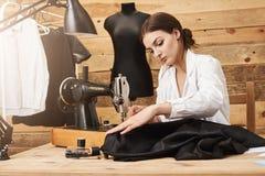 Het naaien is niet alleen het werk, is het talent Creatieve ontwerper die met naaimachine onder haar nieuwe kledingstuklijn werke royalty-vrije stock fotografie