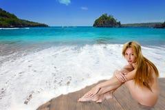 Het naakte meisje op zandige kust bij een overzeese rand. Royalty-vrije Stock Afbeelding