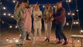 Het nachtleven van de jeugd, bedrijf van vrienden heeft pret en verrukkingsrust op zandig strand stock videobeelden