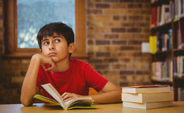 Het nadenkende boek van de jongenslezing in bibliotheek royalty-vrije stock fotografie