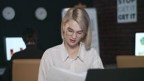 Het nadenkende document van de bedrijfsvrouwenlezing op laptop in donker bureau stock video