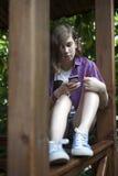 Het nadenkende meisje in een plaidoverhemd leest het nieuws op de telefoon zit Royalty-vrije Stock Afbeelding
