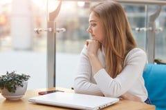 Het nadenkende meisje kijkt opzij in venster terwijl het zitten bij koffie Het charmeren van vrouwelijke dromen en denkt over toe stock afbeelding
