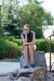 Het nadenkende meisje op een steen Stock Fotografie