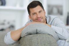 Het nadenkende mens ontspannen op bank thuis royalty-vrije stock fotografie