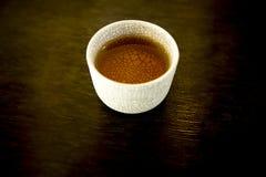 Het nader uitwerken heerlijke drinkt welkom water in het kleine ceramische glas van de patroondecoratie op de donkere bruine patr Royalty-vrije Stock Afbeeldingen