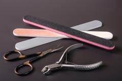 Het nagelschaartje dient en clippers in om de producten van de opperhuidzorg op een donkere achtergrond te verwijderen Stock Afbeelding