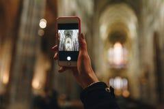 Het nemen van beeld met telefoon in kathedraal stock foto