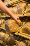 Het nemen van brood van de plank stock fotografie