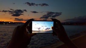 Het nemen van een beeld met een telefoon bij zonsondergang royalty-vrije stock afbeeldingen
