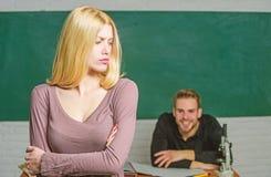 Het nemen van een examen Vrouwelijke student met schoolmeester bij onderzoek Mooie vrouwen bevindende handen die in klaslokaal wo stock afbeelding