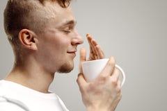 Het nemen van een koffiepauze Knappe de koffiekop van de jonge mensenholding, die terwijl status tegen grijze achtergrond glimlac stock afbeeldingen