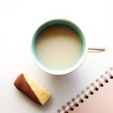 Het nemen van een onderbreking van het werk met mok van thee, koekje en notitieboekje Royalty-vrije Stock Afbeelding