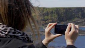 Het nemen van foto's bij de Kust van de Reuzenverhoogde weg in Noord-Ierland stock footage