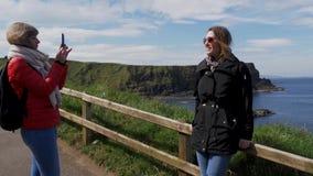 Het nemen van foto's bij de Kust van de Reuzenverhoogde weg in Noord-Ierland stock video