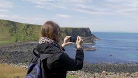Het nemen van foto's bij de Kust van de Reuzenverhoogde weg in Noord-Ierland stock videobeelden