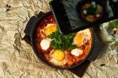Het nemen van foto van traditionele shakshuka met eieren, tomaten en peterselie in een pan, close-up stock fotografie