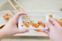 Het nemen van foto van zalmsushi in eetstokjes stock fotografie