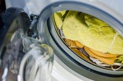 Het nemen van kleren uit wasmachine stock afbeeldingen