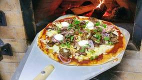 Het nemen van pizza van oven Stock Fotografie
