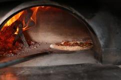 Het nemen van smakelijke pizza van oven in restaurant stock afbeeldingen