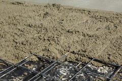 Het netwerk van het versterkingsstaal met vers ruw beton gedeeltelijk wordt behandeld dat Royalty-vrije Stock Afbeelding