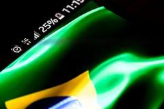 Het netwerk van Smartphone 5G 25 percentenlast en de vlag van Brazilië stock afbeelding