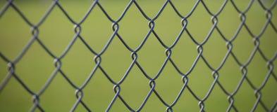 Het netwerkomheining van de staaldraad met groene vage achtergrond Sluit omhoog mening met details stock foto