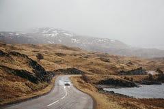 Het niet geïdentificeerde auto drijven op een weg die door Schotse Hooglanden dichtbij Lochinver, Schotland gaat stock afbeeldingen