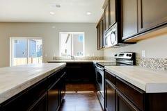 Het nieuwe binnenland van de huiskeuken met donkere bruine kabinetten. Stock Foto