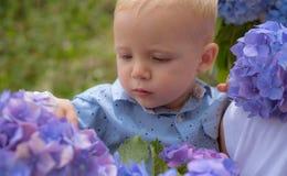 Het nieuwe Concept van het Leven De lentevakantie De Dag van kinderen Kleine babyjongen Weinig jongen bij bloeiende bloem De zome royalty-vrije stock afbeelding