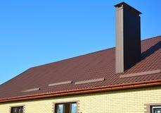 Het nieuwe geïnstalleerde bruine metaal betegelde dak met plastic dakgootsysteem, de bescherming van de sneeuwraad, schoorsteen,  Stock Fotografie