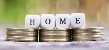 Het nieuwe huis koopt - geldmuntstukken met brieven Stock Foto