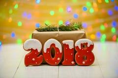 Het nieuwe jaar 2018 maakte met peperkoekkoekjes met bokeh en het patroon van de lensgloed op gouden achtergrond, exemplaarruimte Stock Foto's