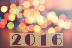 Het nieuwe jaar 2016 vormde zich op houten blokken en defocused bokeh de achtergrond van Kerstmislichten Royalty-vrije Stock Afbeelding