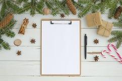 Het nieuwe Lege klembord van het jaarprototype en Kerstmisdecoratie op witte houten achtergrond Vlak leg, hoogste mening Om te do stock afbeelding
