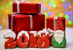 Het nieuwe symbool van het jaar 2018 teken maakte met peperkoekkoekjes, santa en rode giftdozen met bokeh en het patroon van de l Stock Afbeeldingen
