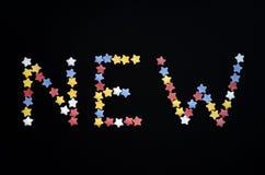 Het Nieuwe woord wordt geschreven in dik type van de sterren van het suikergebakje op een zwarte achtergrond, voor, reclame, hand stock foto's