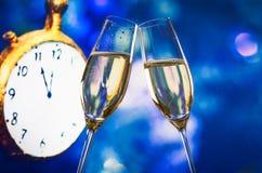 Het nieuwjaar of Kerstmis bij middernacht met champagnefluiten maakt tot toejuichingen blauwe bokeh en klok Stock Foto's