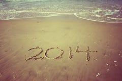 Het nieuwjaar 2014 is komend concept dat op strandzand wordt geschreven. uitstekend effect Stock Afbeelding