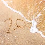 Het nieuwjaar is komend concept - inschrijving 20 op een strandzand, overzeese golf behandelt cijfers 2017 of 2018 Nieuw jaar Royalty-vrije Stock Foto