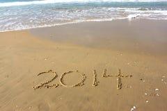 Het nieuwjaar 2014 is komend die concept op strandzand wordt geschreven Royalty-vrije Stock Afbeeldingen
