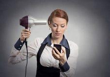 Het nieuws van de vrouwenlezing op smartphoneholding hairdryer royalty-vrije stock afbeelding