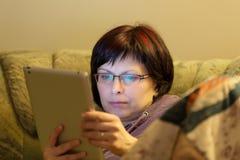 Het nieuws van de vrouwenlezing op tablet stock afbeeldingen
